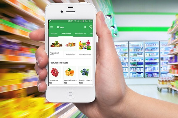 a person holding an iphone with mi grocery app