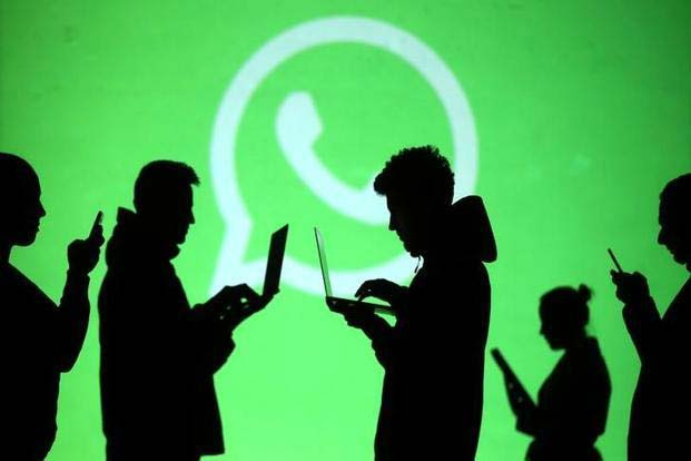 some persons walking with laptop with whatsapp logo background