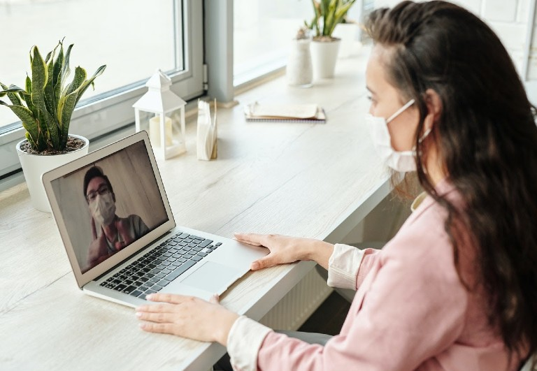a woman wearing mask an sitting in front of the laptop